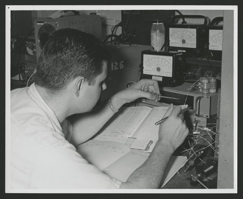 George Ludwig recording data tape playback into his personal notebook