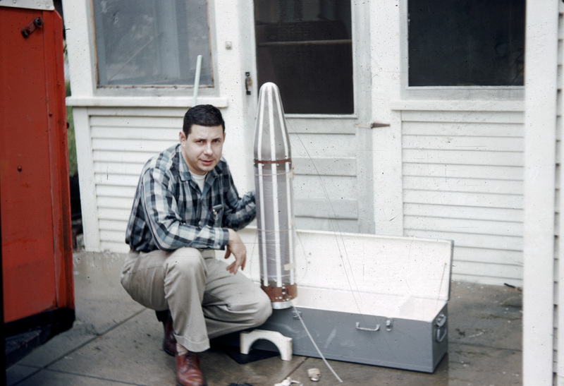 George Ludwig squating beside the Explorer 1 satellite before loading it into his car