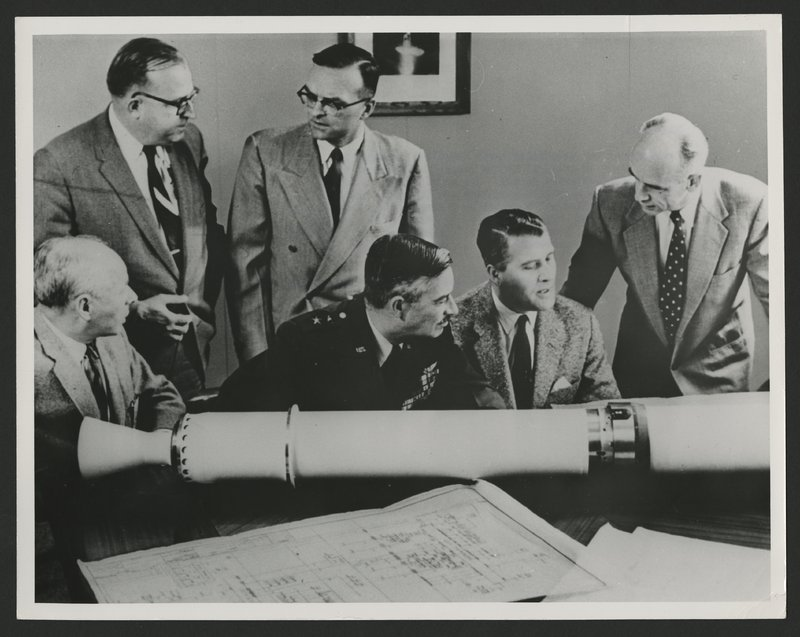 Mr. Eberhard Reese, Major General J.B. Medaris, Dr. Wernher von Braun and Dr. Ernst Stuhlinger (sitting) and Mr. W.A. Mrazak and Dr. Walter Haeussermenn (standing) around the to size prototype model of Explorer I