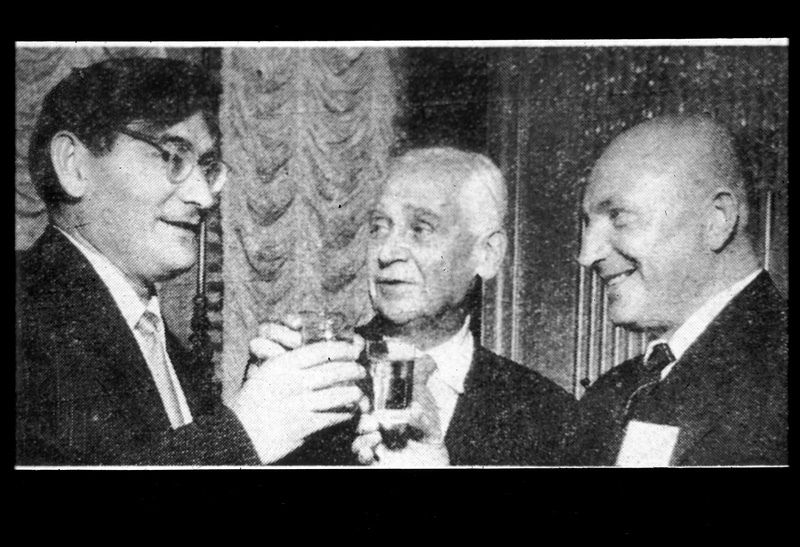 Three Russian men celebrate the successful launch of Sputnik by clinking their glasses together in a toast