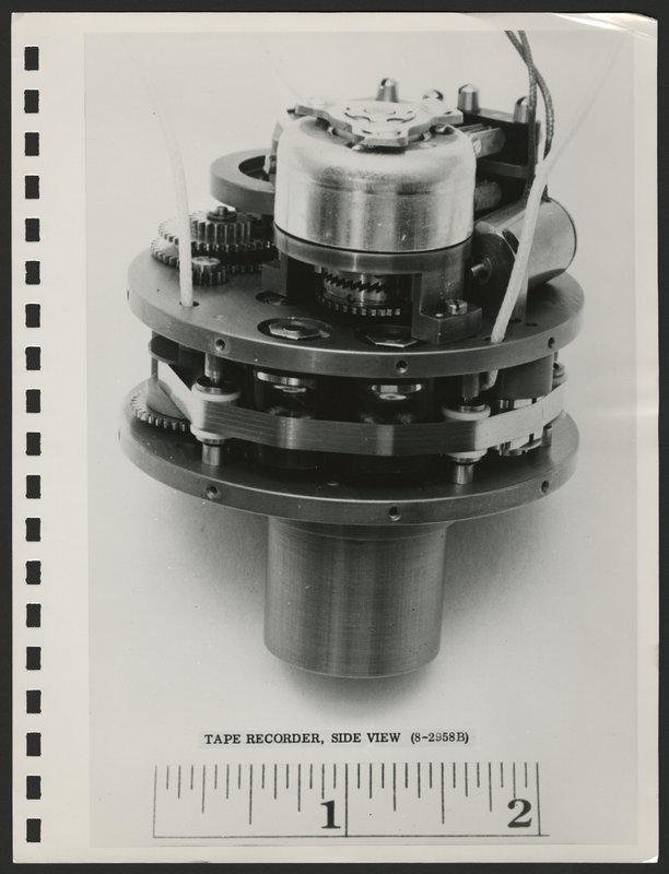 Photograph of Explorer 1 tape recorder from the side with scale. The component is two inches in diameter