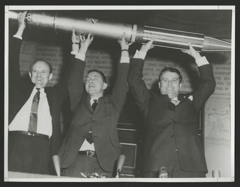 The Explorer 1 team, from left to right: William Pickering, James Van Allen, and Wernher von Braun, holding the replica triumphantly above their heads.