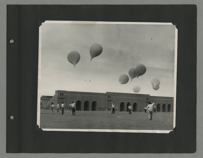 State University of Iowa students releasing weather ballons in front of Kinneck Stadium from Leslie Meredith's scrapbook, 1951-1955