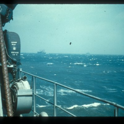 slide of several expediation ships on water, photo taken from bow of ship