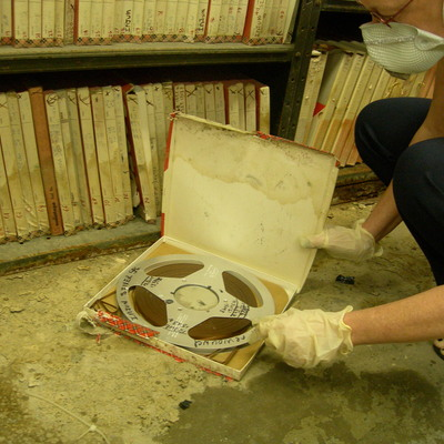 Exposed magnetic data tape reel in soiled, damp original box with mold growth