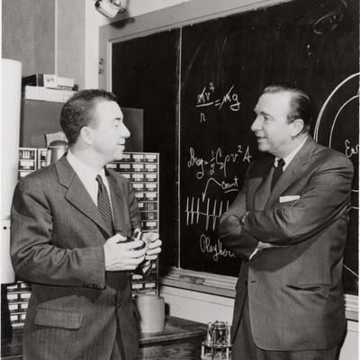James Van Allen talking with Walter Cronkite in front of a chalk bord with equations and diagrams on it