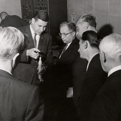 George Ludwig holding a replica of Explorer 1 rocket while talking with a group of curious men in suits