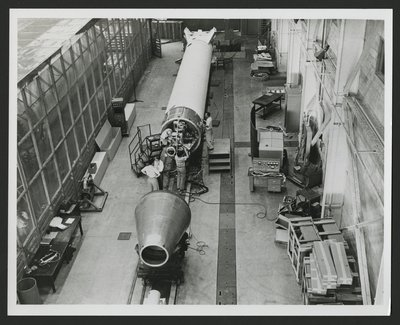 Several men attaching satellite system to the Vanguard rocket